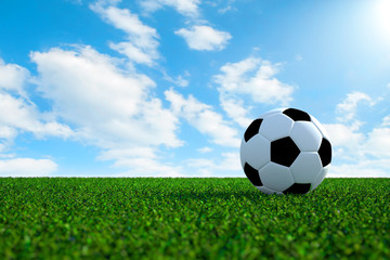 Soccer ball on field with sky background