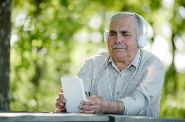 Elderly man listening to music on a tablet