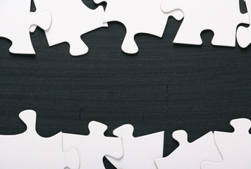 A border of blank white jigsaw puzzle pieces on a blackboard