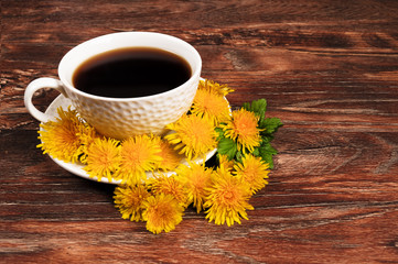 Coffee mug surrounded by dandelions on a wooden background.