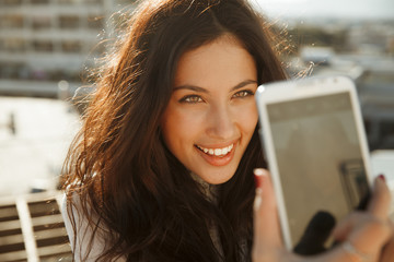 smiling woman take a picture of herself with a smartphone.