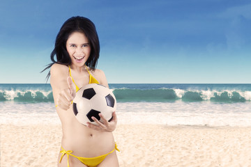 Excited woman in bikini holding soccer ball 1