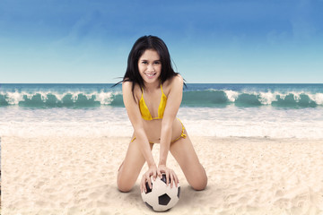 Excited woman in bikini holding soccer ball