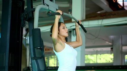 Sports young woman doing exercises on Lat Machine.