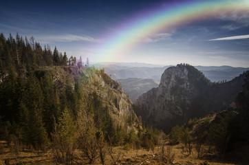 mountain on sunny summer day with rainbow after rain