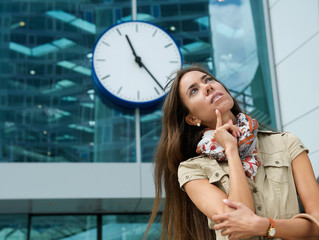Young woman thinking with clock in background