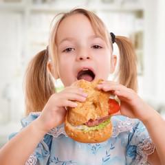 Kind ißt ein Brötchen mit Belag