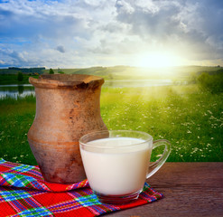 Ancient clay pot and mug of milk on the background of beautiful