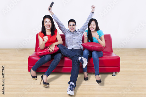 Happy young friends watching tv at home