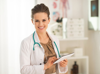 Smiling medical doctor woman using tablet pc