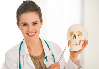 Happy medical doctor woman showing human skull
