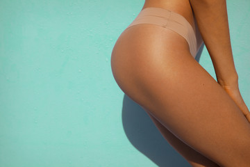 Sexy woman buttock on turquoise background.