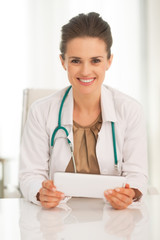 Portrait of happy medical doctor woman using tablet pc