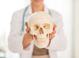 Closeup on medical doctor woman showing human skull