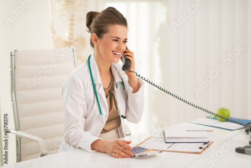 Happy medical doctor woman talking phone