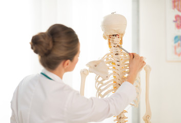 Medical doctor woman teaching anatomy using human skeleton model