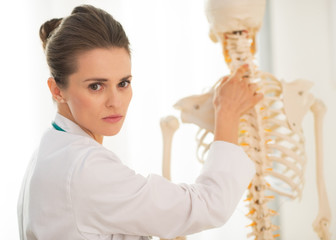Portrait of medical doctor woman showing spine on human skeleton