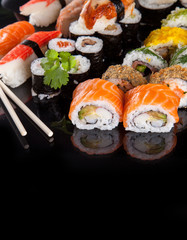 Delicious sushi pieces on black background