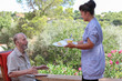 carer giving senior food in residential home