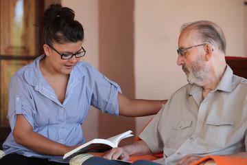companion or granchild reading to senior or grandfather