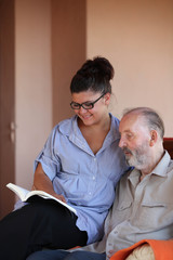 young person reading to elderly man