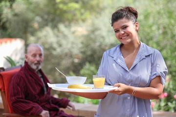 home carer serving meal to elderly man
