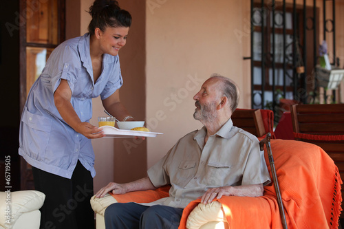 nurse or helper in residential home giving food to senior man - 65719505