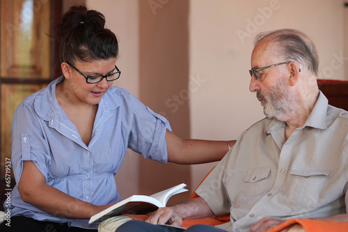 companion or granchild reading to senior or grandfather - 65719537
