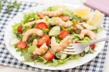 closeup of fork with fresh shrimp and berry salad with lettuce a