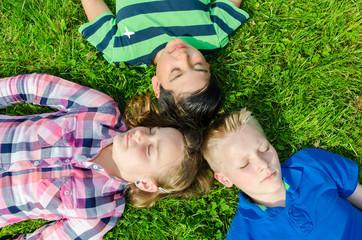 kinder liegen relaxt im gras