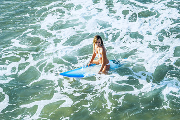 Young attractive surfer in surf on surfboard