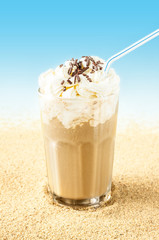 Frappe - iced coffee on beach background