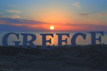 Seascape with sunset and white word Greece on sand
