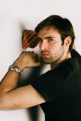 Portrait of handsome guy in a black T-shirt and watch on a hand