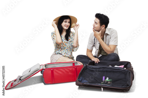 Two tourists opening luggage