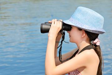 teen girl looking through binoculars side view