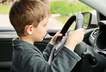 boy driving a car and looking at the way