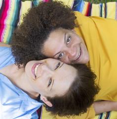two woman lying on blanket