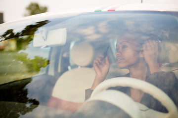 Young black woman applying mascara in car