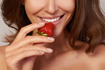 Beatiful girl smile and eat red strawberry