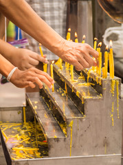 Hands of Buddhists lighting up the candles on altar to pay their
