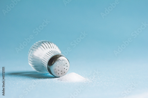 Fotobehang Kruiderij Spilled salt and saltshaker on blue background