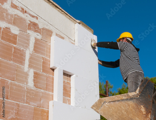 worker mounts sheets of polystyrene on external vertical walls - 65725183