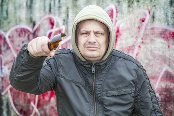 Man with broken glass beer bottle near wall