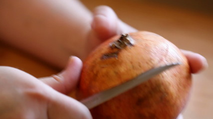 woman cuts knife pomegranate