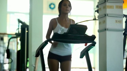 Young woman doing exercises on treadmill in gym. At the end of