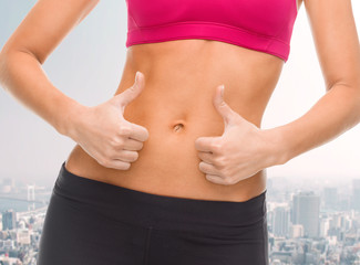 close up of female abs and hands showing thumbs up