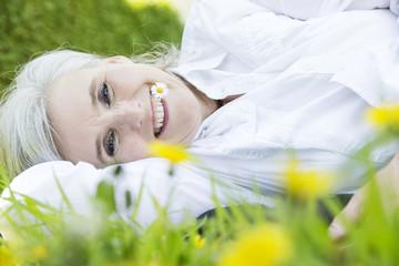 Frau,Bestager,grauhaarig mit Gänseblümchen im Mund