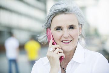 frau,50,grauhaarig telefoniert mit handy