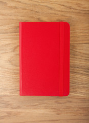 Red copybook with elastic band on wooden background.